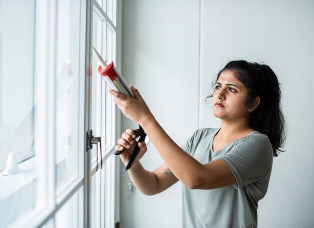Mulher usando uma pistola de silicone para consertar uma janela