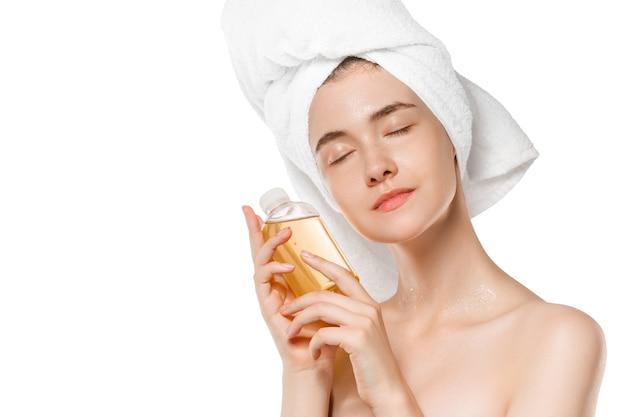 Mulher usando uma toalha fazendo sua rotina diária de cuidados com a pele, isolada no branco