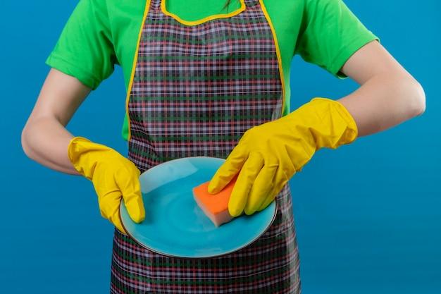 Mulher usando uniforme com luvas lavando pratos na parede azul isolada