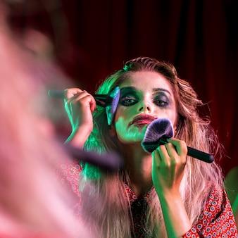 Mulher usando vários pincéis no rosto