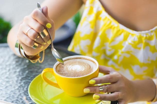 Mulher usando vestido amarelo, bebendo café. jovem garota irreconhecível com manicure amarelo ao ar livre. feche os dedos com esmalte brilhante