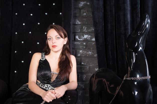 Mulher usando vestido formal preto sentada no trono ao lado da estátua do cachorro na coleira