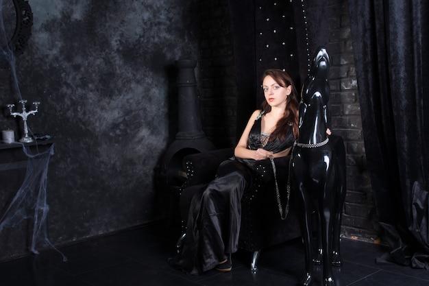 Mulher usando vestido formal preto sentada no trono ao lado da estátua do cachorro usando coleira
