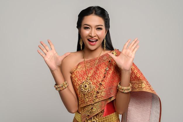 Mulher usando vestido tailandês que fez um símbolo de mão