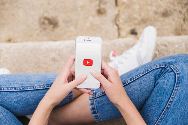 Mulher, usando, youtube, app, ligado, telefone móvel
