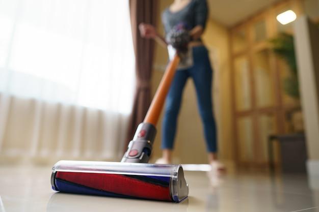 Mulher usar aspirador de limpeza no chão.