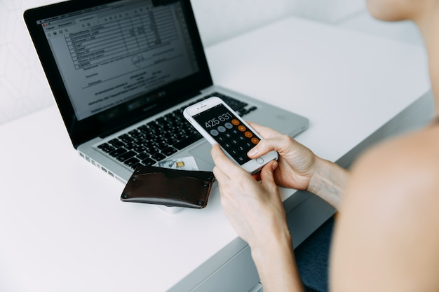 Mulher usar telefone com calculadora aberta e segurando o cartão de crédito com compras on-line perto de laptop