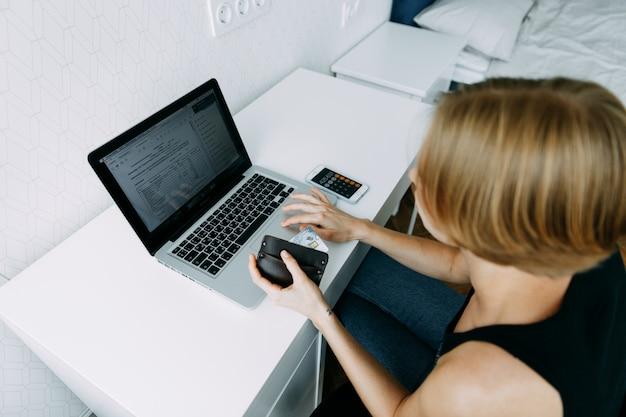 Mulher usar telefone inteligente e segurando o cartão de crédito com compras on-line perto de laptop