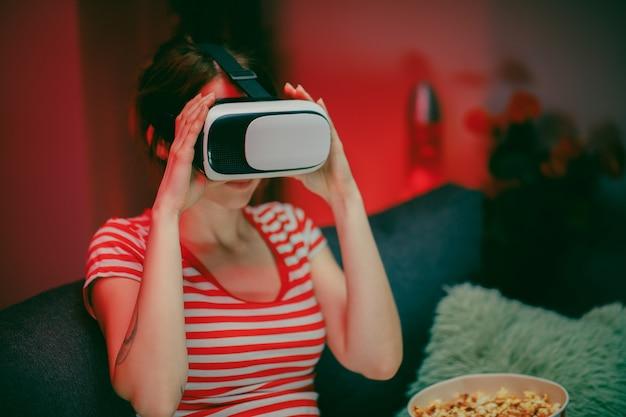 Mulher usar vr fone de ouvido jogando videogame. mulher relaxante jogando videogame usando o fone de ouvido vr. jogador feminino caucasiano.