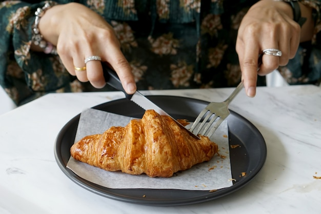 Mulher, uso, faca garfo, corte, croissant, ligado, a, prato preto, para, comer