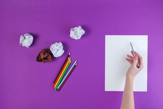 Mulher vai desenhar com lápis de cor sobre uma superfície roxa com bolas de papel amassado.