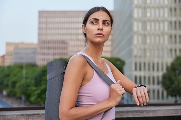 Mulher vai praticar ioga avançada verifica os resultados do treino em poses de relógio de fitness na cidade