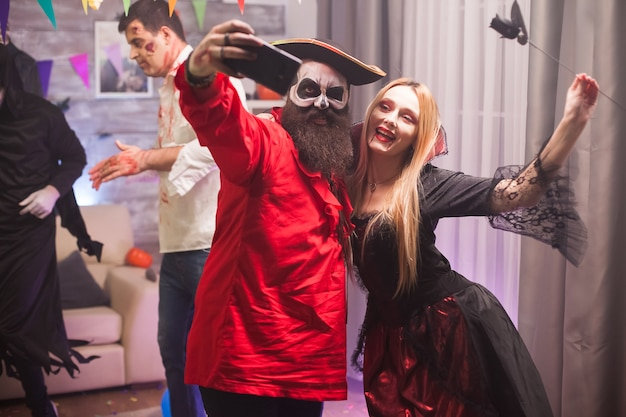 Mulher vampira feliz e homem pirata tirando uma selfie na celebração do halloween.