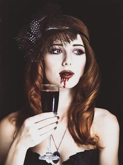 Mulher vampira ruiva com copo de sangue. foto em estilo vintage.