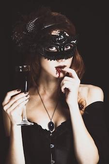 Mulher vampira ruiva na máscara com um copo de sangue. foto em estilo vintage.