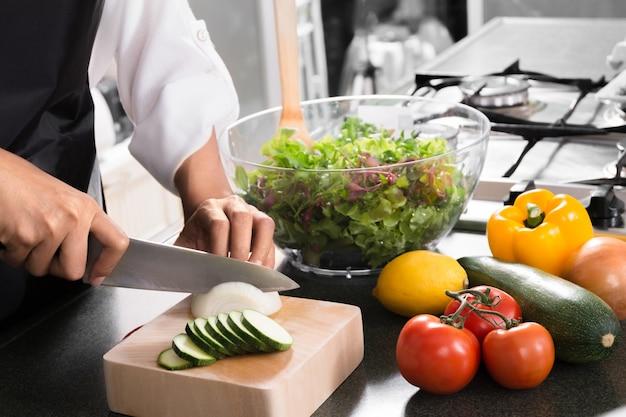 Mulher vegana comendo alimentos saudáveis e preparando salada para jantar em uma cozinha