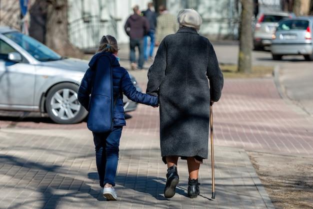 Mulher velha andando na rua com bengala e uma menina vai com ela.