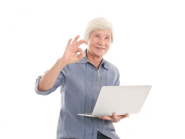 Mulher velha asiática usar computador portátil em fundo branco