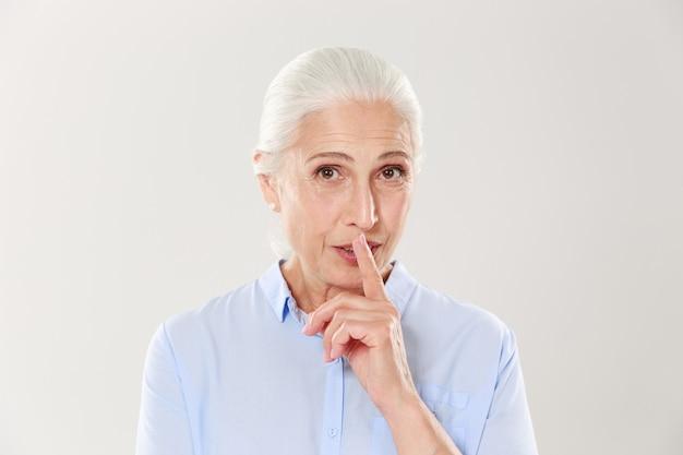 Mulher velha bonita mostrando o gesto de silêncio