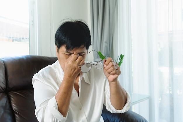 Mulher velha cansada removendo os óculos, massageando os olhos depois de ler o livro de papel. sensação de desconforto devido ao uso prolongado de óculos, dor nos olhos ou dor de cabeça