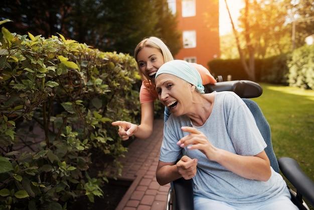 Mulher velha com câncer está sentado em uma cadeira de rodas.