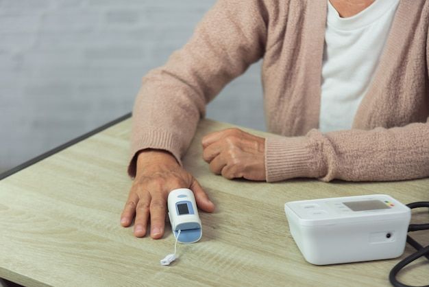 Mulher velha com tonometer, verificar o nível de pressão arterial