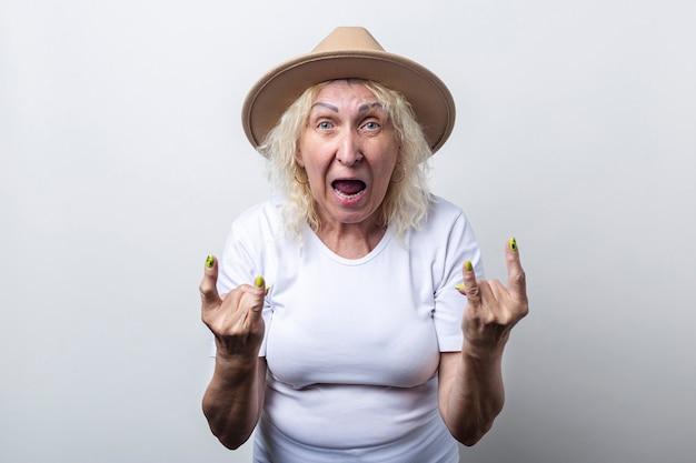 Mulher velha com um chapéu mostra um gesto de chifre de roqueiro sobre um fundo claro.
