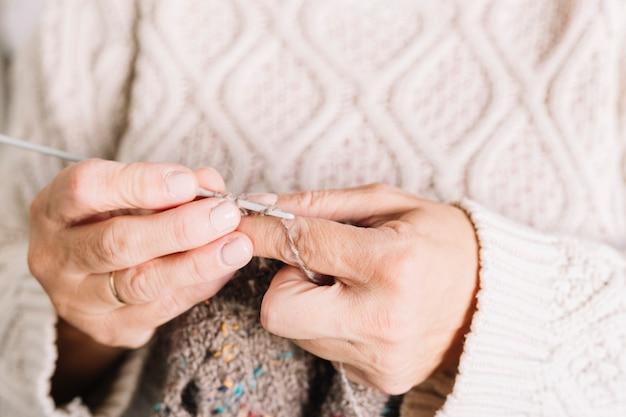 Mulher velha, em, suéter, tricotando, echarpe