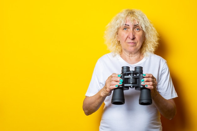 Mulher velha em t-shirt branca segurando binóculos na parede amarela.
