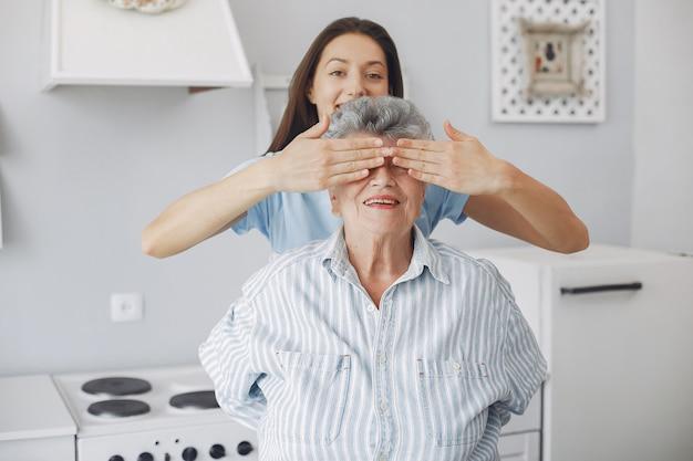 Mulher velha em uma cozinha com jovem neta