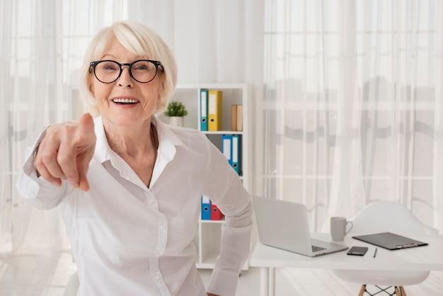 Mulher velha feliz em seu escritório