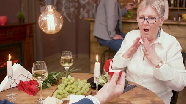 Mulher velha olhando chocada com o anel que seu marido deu. pedindo que ela se casasse com ele.
