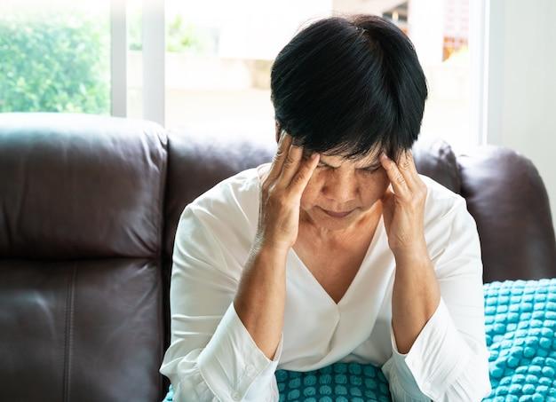 Mulher velha que sofre de dor de cabeça, estresse, enxaqueca, conceito de problema de saúde