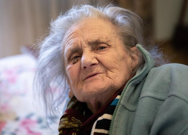 Mulher velha. retrato de uma mulher muito velha e cansada em depressão, sentada dentro de casa na cama