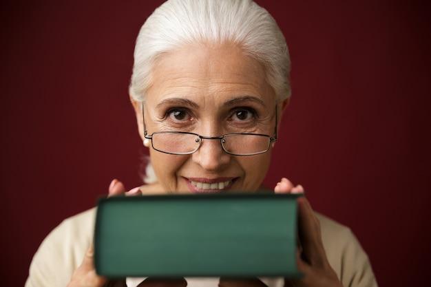 Mulher velha, sentando, segurando livro