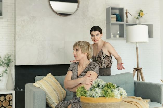 Mulher velha triste está sentado em um sofá em uma sala, enquanto sua filha adulta grita com ela.