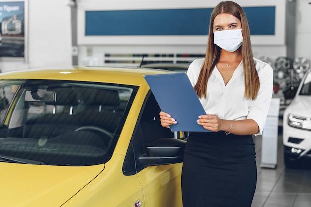 Mulher vendedora de carros perto de um carro novo usando máscara protetora em uma concessionária