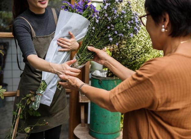 Mulher vendendo flores para seu cliente