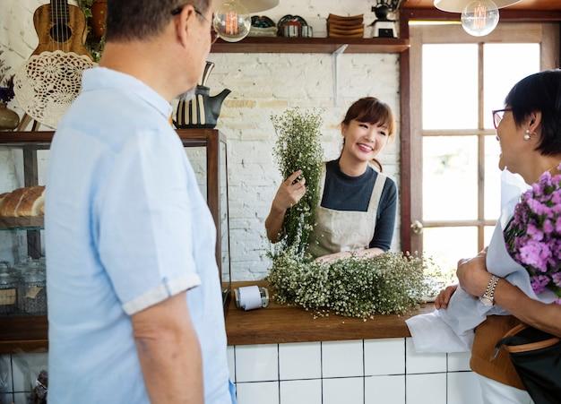 Mulher vendendo flores para um casal