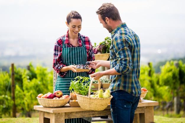 Mulher vendendo legumes orgânicos para homem