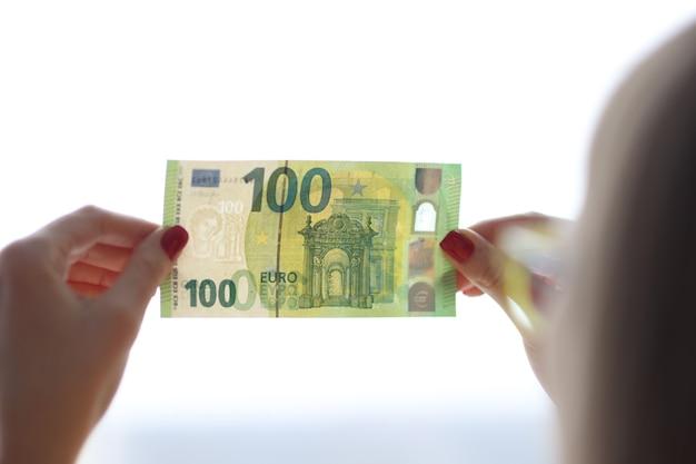 Mulher verifica a autenticidade do conceito de dinheiro falsificado de notas de cem euros