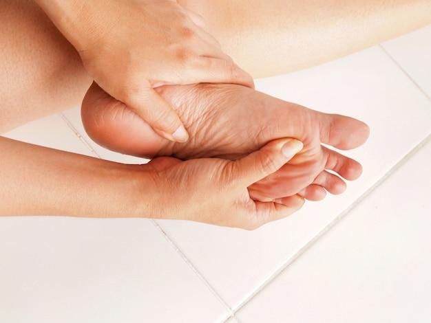 Mulher verifica seu pé dolorido
