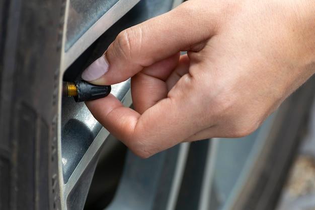 Mulher verificando a calibração dos pneus do carro. manutenção de veículos