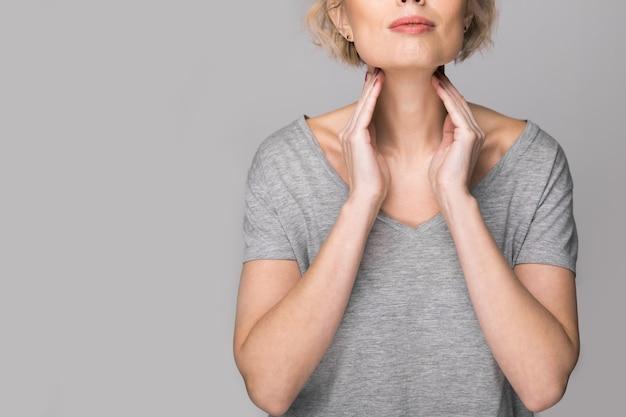 Mulher verificando a glândula tireóide sozinha. perto da mulher de camiseta branca, tocando o pescoço com uma mancha vermelha. o distúrbio da tireoide inclui bócio, hipertireoidismo, hipotireoidismo, tumor ou câncer. assistência médica.
