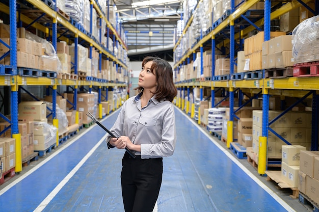 Mulher verificando e contando os produtos na prateleira do grande depósito e depósito