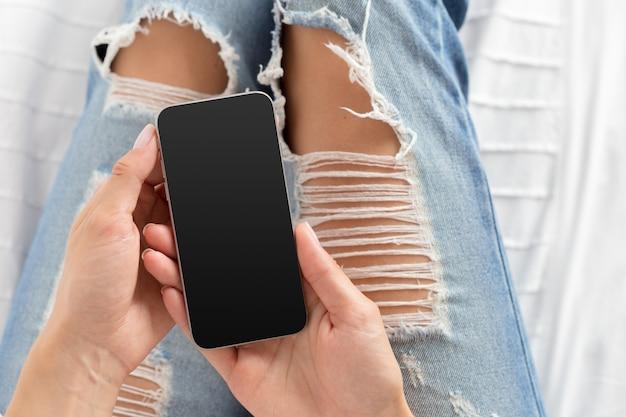Mulher verificando o celular na cama