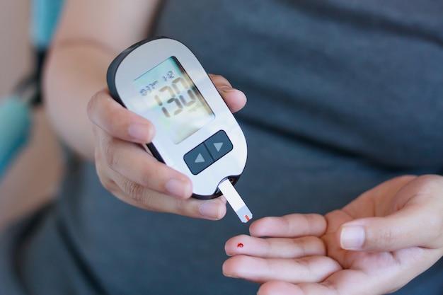 Mulher verificando o nível de açúcar no sangue com glicosímetro