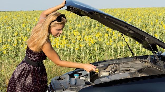 Mulher verificando o nível do óleo do motor em seu carro, que quebrou ao lado de um campo de girassóis