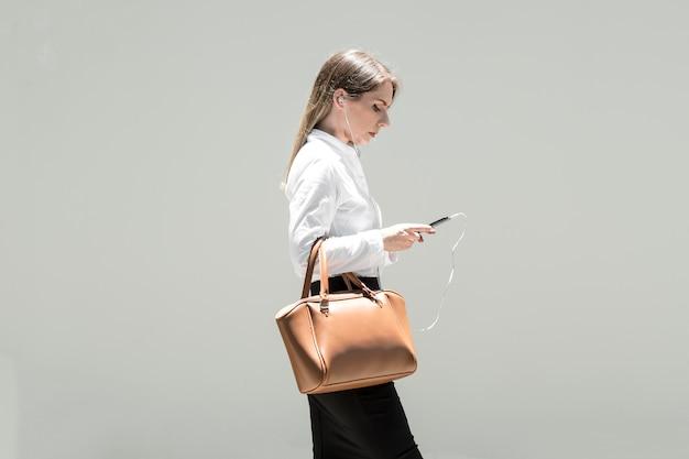 Mulher verificando o telefone a caminho de casa