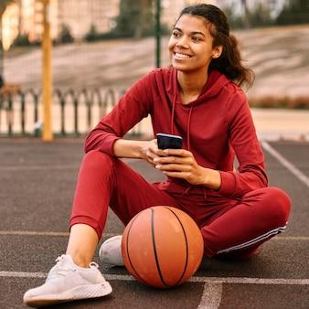 Mulher verificando o telefone ao lado de uma bola de basquete
